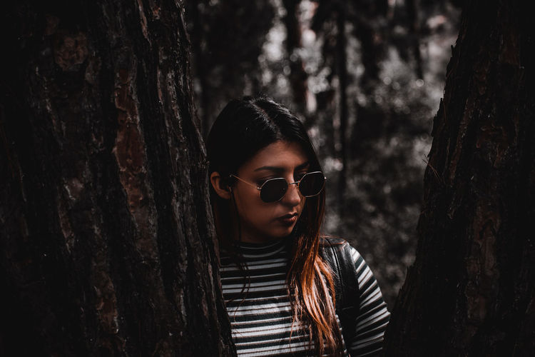 Portrait of beautiful young woman standing by tree trunk