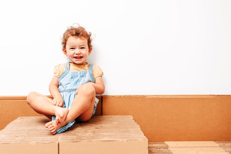 Portrait of smiling girl sitting against wall at home