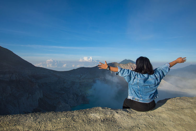 Rear View Of Woman With Arms Outstretched Sitting On Mountain