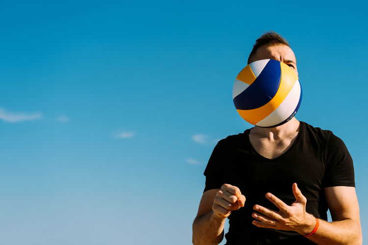 Low angle view of man standing against blue sky with a volleyball in mand