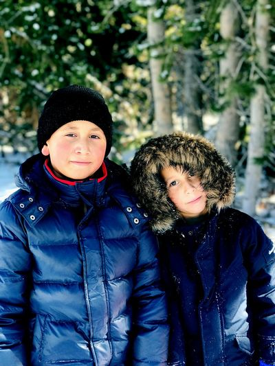 Portrait of siblings in warm clothing standing against trees