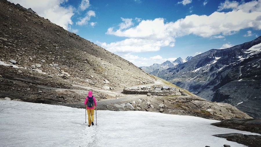 Rear view of woman walking on snowcapped mountain against sky