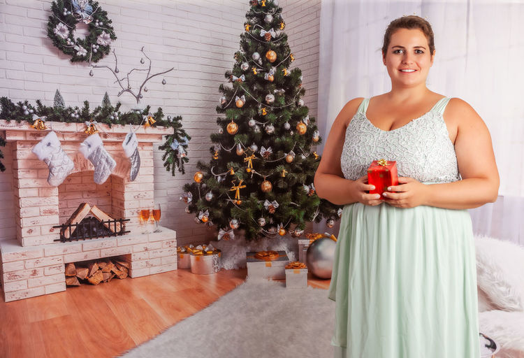 Portrait of smiling woman standing by christmas tree