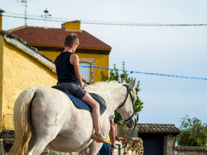 Boy riding horse by house against sky
