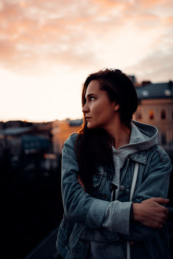 Young woman looking away while standing against sky during sunset