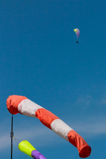 Low angle view of windsock against blue sky