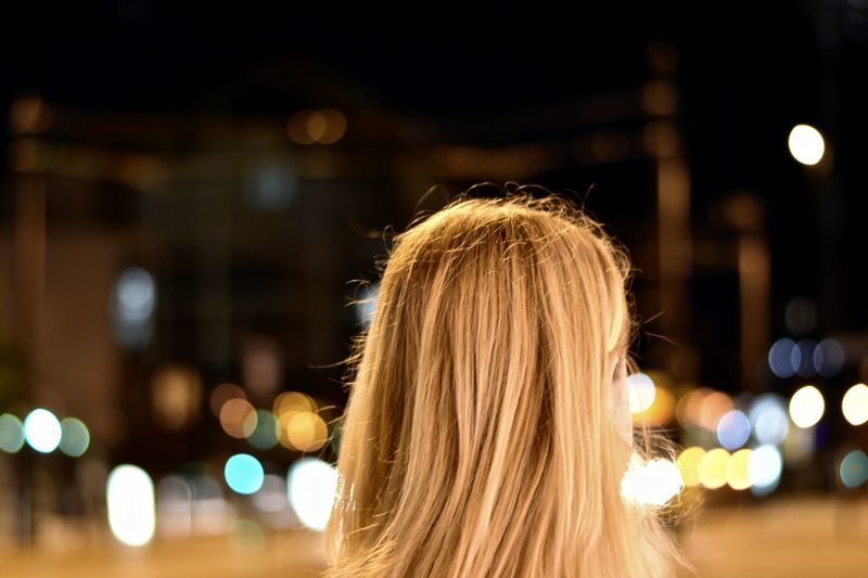 Rear view of woman against illuminated city at night