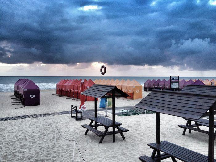 Empty beach against cloudy sky