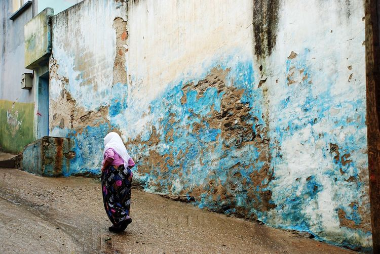 Rear View Of Woman Walking On Street Against Weathered Wall