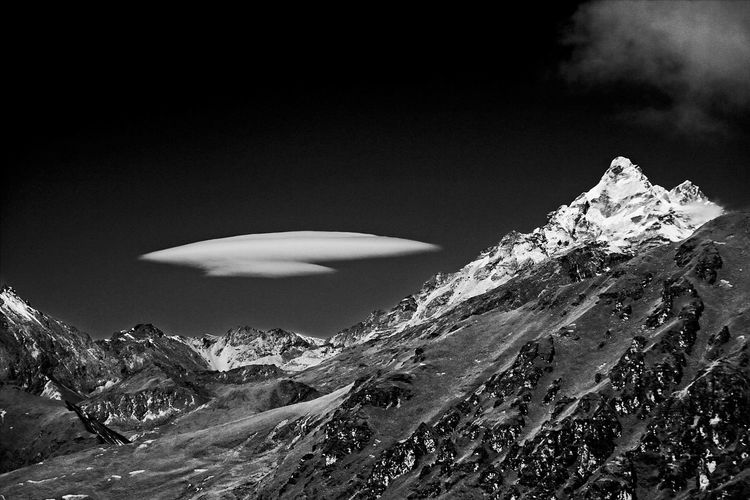 Scenic view of snowcapped mountains and lenticular clouds against sky
