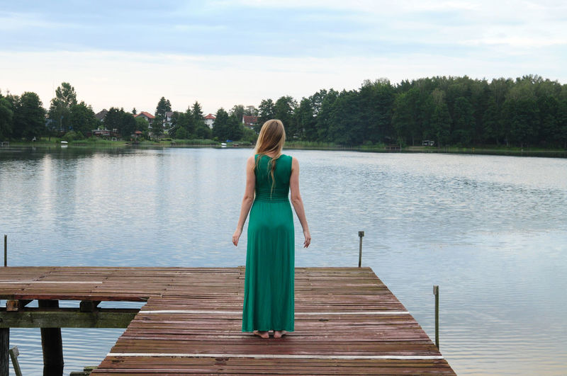 Rear View Of Woman Standing On Pier Over Lake Against Sky