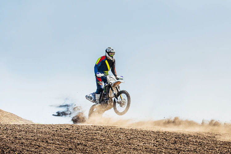 Man riding motorbike against sky
