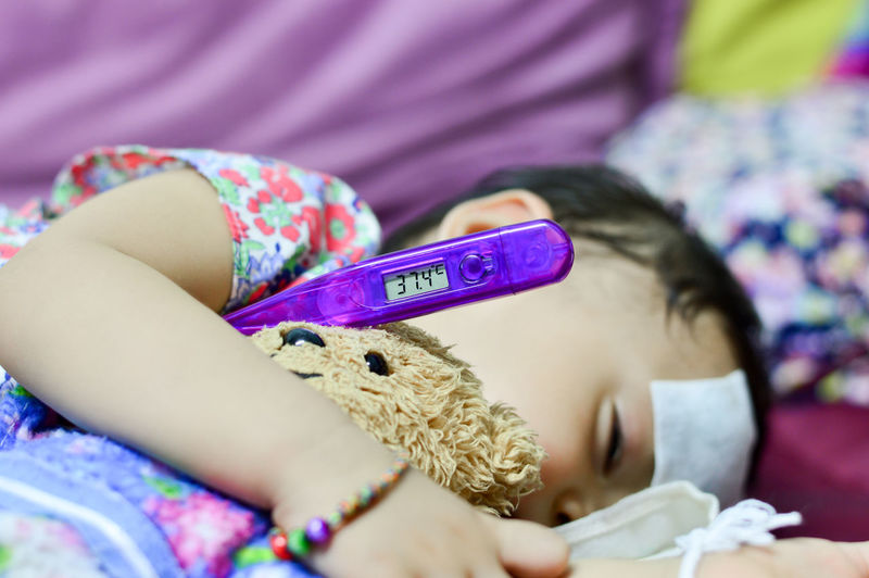 Sick baby lying measuring electric thermometer Child Childhood One Person Girls Indoors  Lying Down Real People Holding Women Lifestyles Relaxation Furniture Bed Casual Clothing Offspring Females Leisure Activity Selective Focus Innocence Sick Themometer