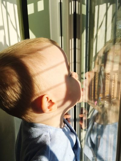 Close-up of cute baby boy touching reflection on glass window