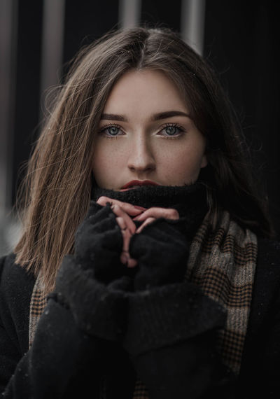 Portrait of beautiful young woman in warm clothing standing outdoors