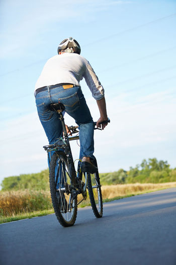 Rear view of senior man cycling on road against sky