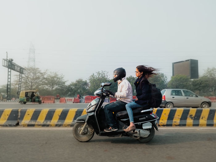 Man riding woman sitting in city against sky