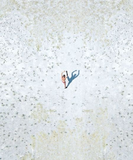 Aerial view of shirtless man walking on snow covered land