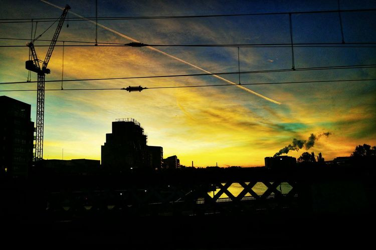 Silhouette bridge and buildings against sky at sunset