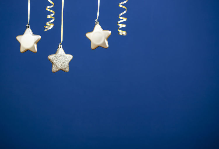 Close-up of christmas decorations hanging against blue wall