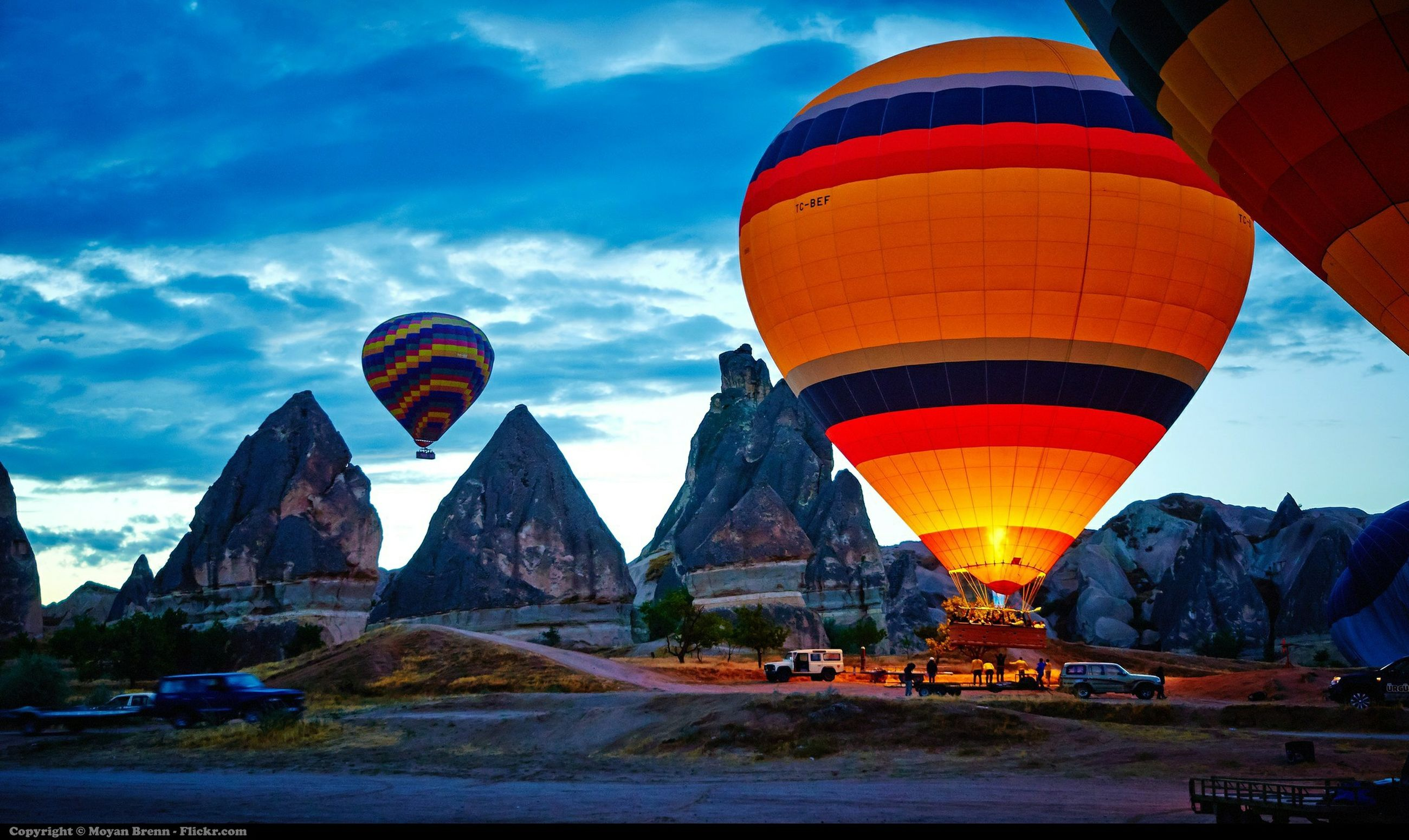 transportation, sky, mode of transport, cloud - sky, built structure, travel, architecture, hot air balloon, mountain, cloud, building exterior, tourism, car, travel destinations, incidental people, flag, outdoors, road, flying, land vehicle