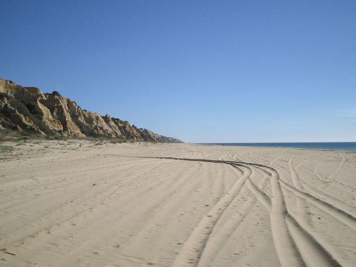 Tracks On Beach Against Blue Sky