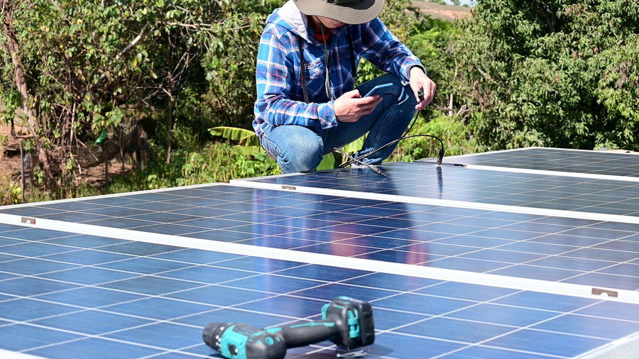Low section of worker using mobile phone while installing solar panel