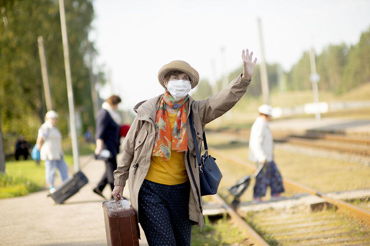 Portrait of positive senior woman wearing a face mask waiting for train due to coronavirus  covid-19