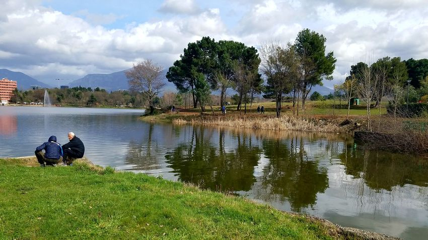 Trees And Nature Beauty In Nature Mountain Range Mountain In The Background Clouds And Sky Artificial Lake Of Tirana Colorful Green Color Cityscape Streetphotography Fishing Time Peoole And Places People Watching