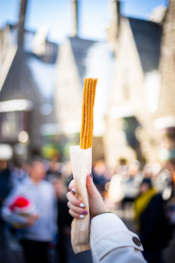 Midsection of woman holding churro in city
