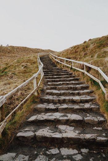 Steps leading towards landscape against sky