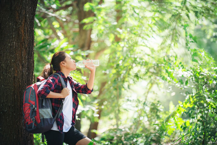 Female Hiker Drinking Water While Leaning On Tree Trunk In Forest