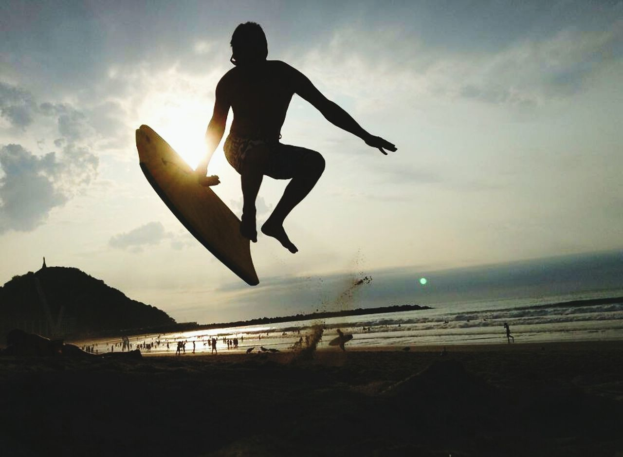 Full length of silhouette person jumping on beach