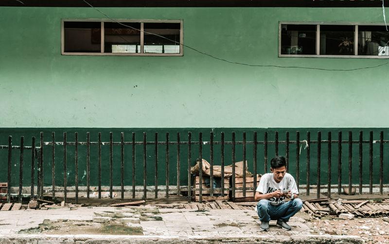 Man sitting on window against building