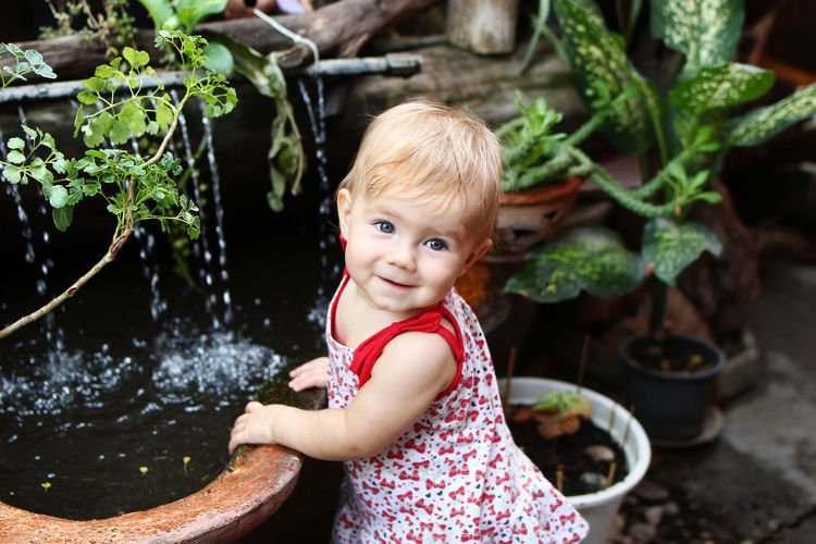 Little smiling girl with blond hair in sundress is standing in garden with pot plants and waterfall.