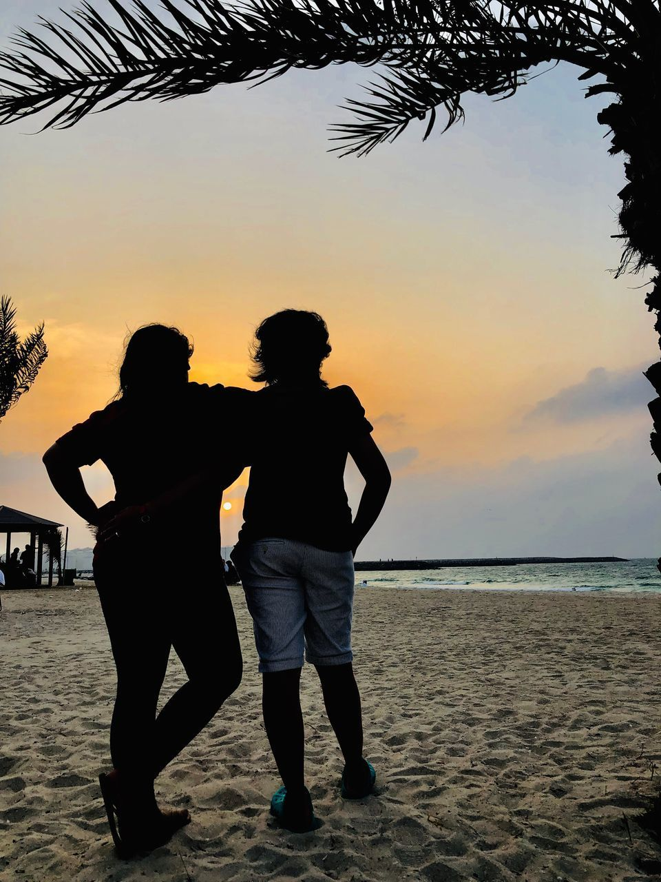 sunset, sky, two people, sea, water, real people, beach, men, leisure activity, togetherness, land, lifestyles, beauty in nature, standing, nature, bonding, full length, love, women, couple - relationship, positive emotion, horizon over water, outdoors, arm around