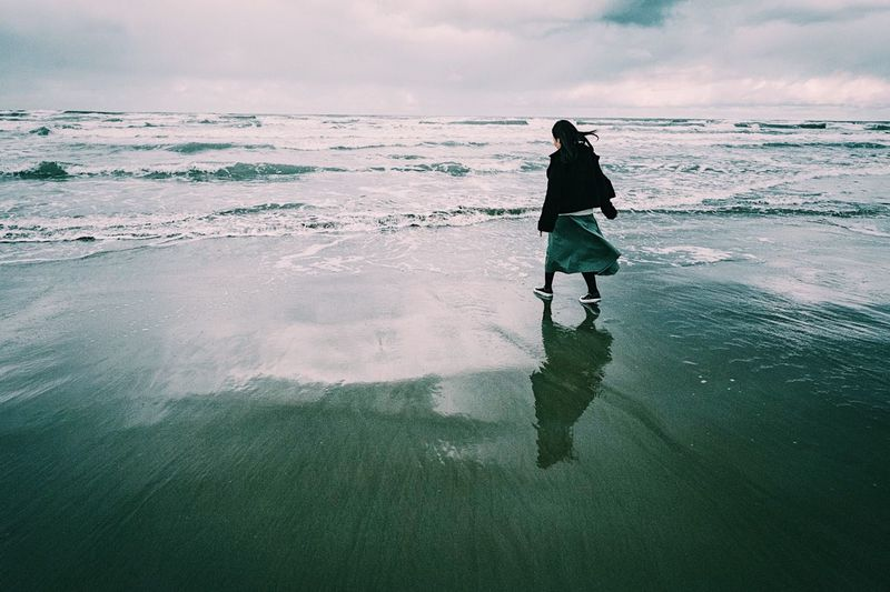 Rear view of woman walking on shore at beach