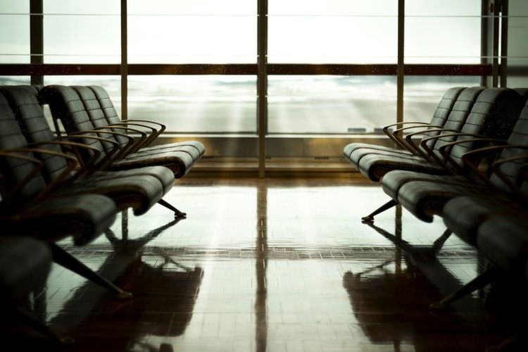 Chairs in airport departure area against glass window