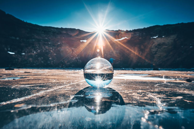 Reflection of crystal ball on water against sky during sunset