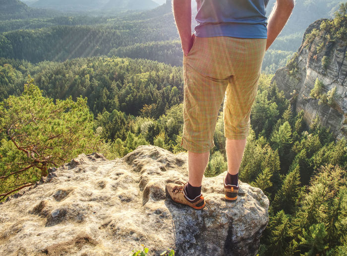 Hiker man stays on the mountain hill during hiking. hker staying on rock and looking down to valley