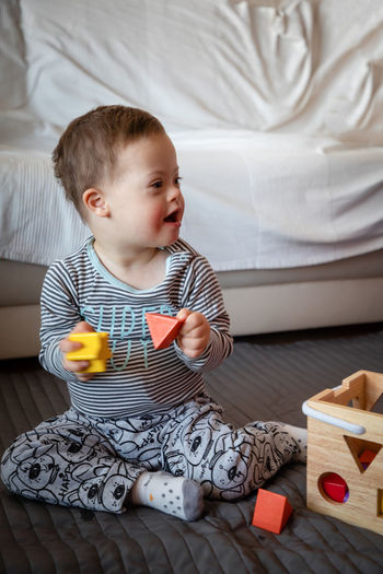 Babyboy Bed Boys Child Childhood Cute Down Syndrome Front View Furniture Home Interior Indoors  Innocence Leisure Activity Lifestyles Looking Males  Men Mental Health  One Person Playing Real People Sitting Toy
