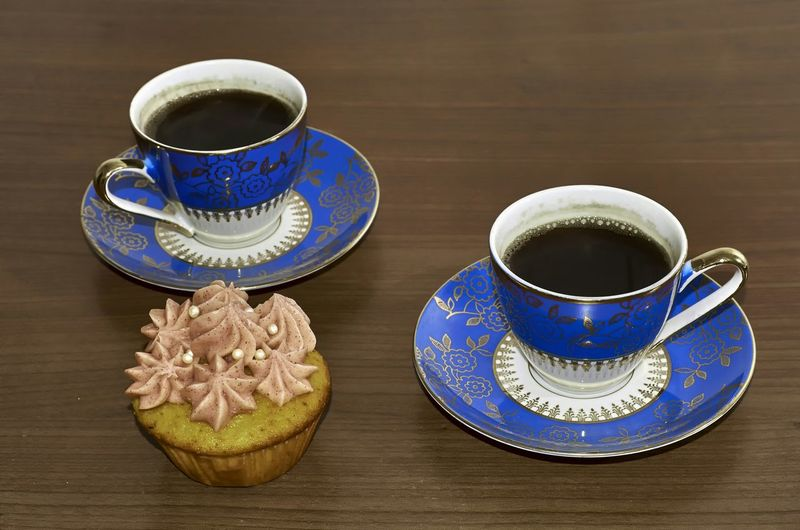High Angle View Of Black Coffee With Cupcake Served On Table