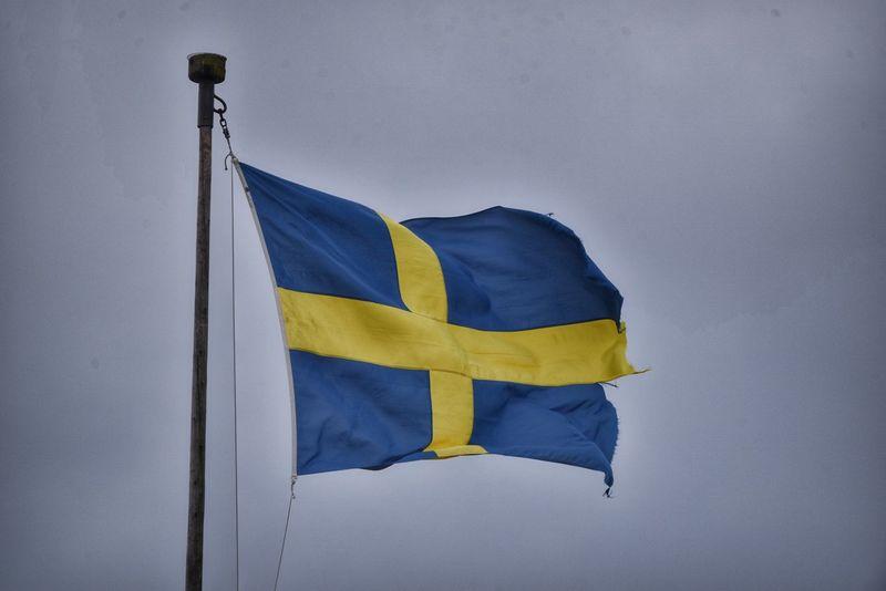 Torned swedish flag waving in the grey sky during an autumn day Swedish Flag Yellow Blue Tornes Sky Sweden 🎈👻 Symbol Patriotism Scandinavia Europe Waving