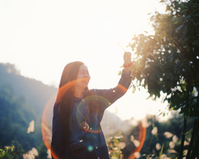 Smiling Woman By Tree Against Sky On Sunny Day
