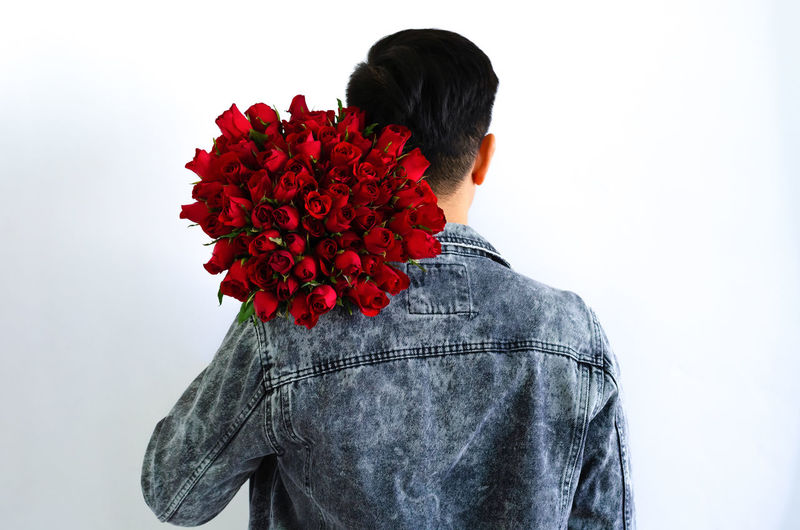 Rear view of man standing by red flower against white background