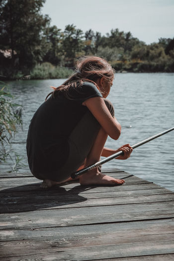 Girl fishing while crouching on pier