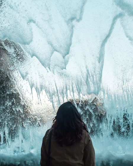 Rear view of woman standing in ice