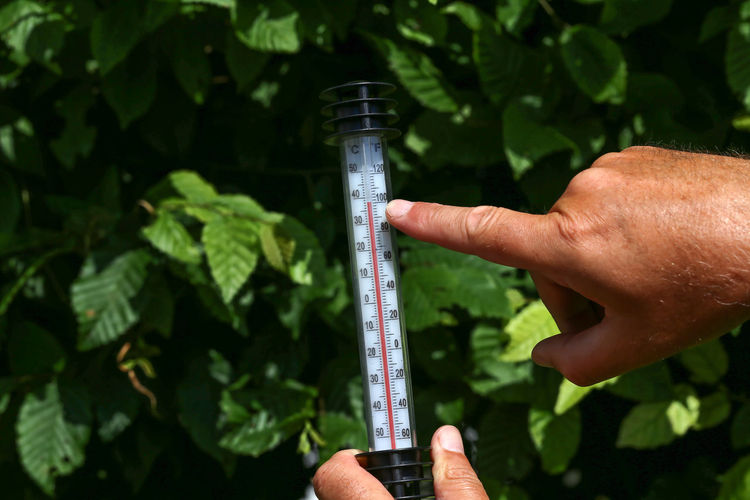 Close-up of hand holding climate thermometer outdoors