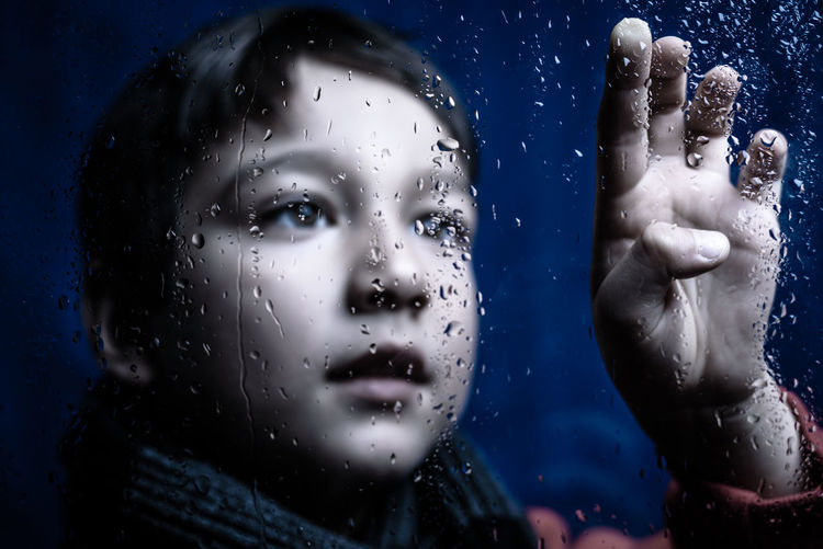 Autumn Calm Hanging Out Interesting Rain Raindrops Reflection Winter Blue Bokeh Boy Child Close-up Cold Drop Headshot Indoors  Mystery Sad Water Wet Window Young Adult Mix Yourself A Good Time The Week On EyeEm AI Now EyeEm Ready   Visual Creativity The Portraitist - 2018 EyeEm Awards My Best Photo