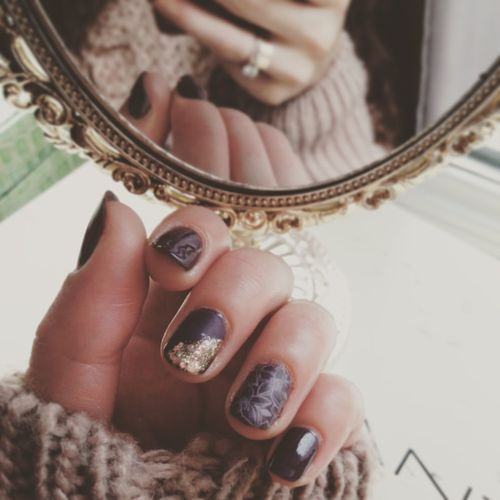 Cropped hand of woman with nail polish reflecting on mirror